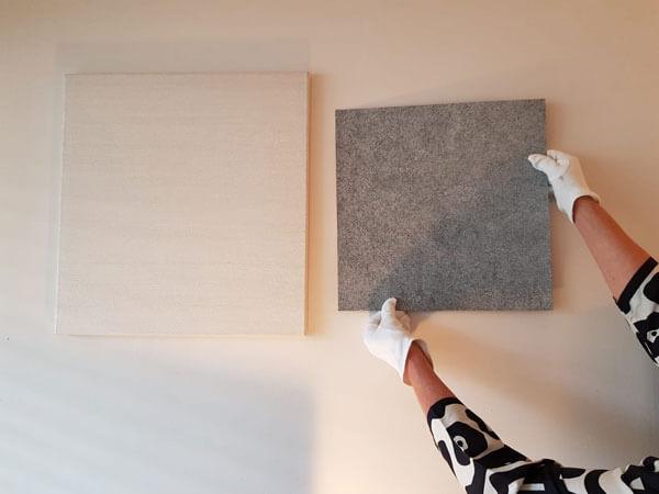 Kunstwerk wordt opgehouden met witte handschoenen naast wit kunstwerk