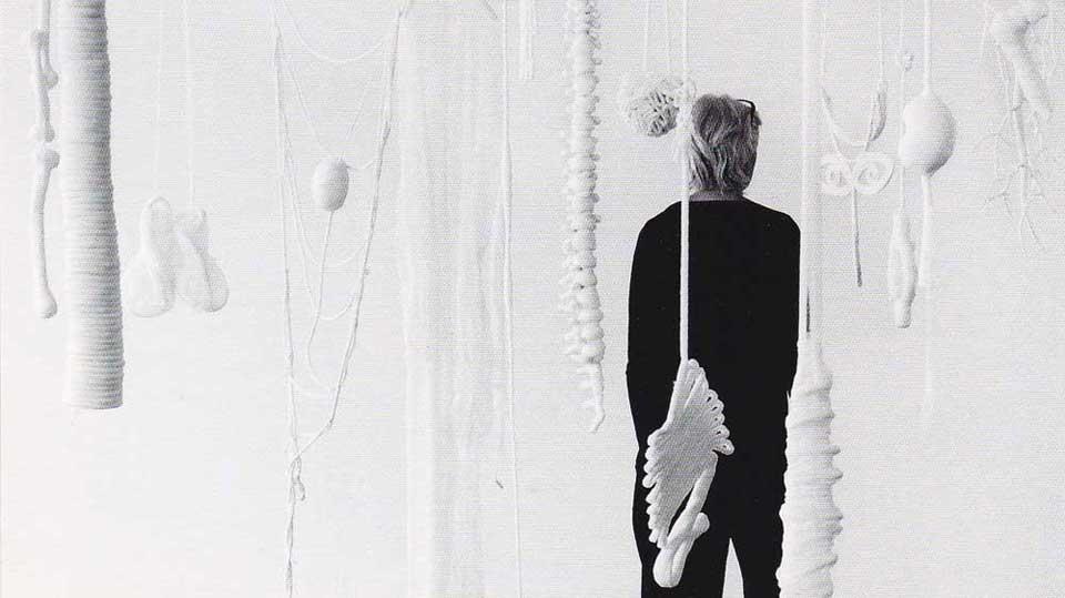Vrouw die op rug gezien in een ruimte staat met witte hangende voorwerpen.
