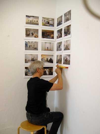 Fotograaf André Smits hangt zijn foto's op de muur.