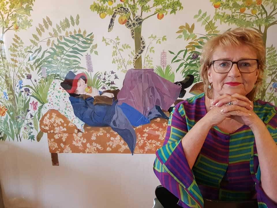 Mirjam Hijstek zit voor een kleurige tekening met daarop een liggende vrouw die een appel eet.