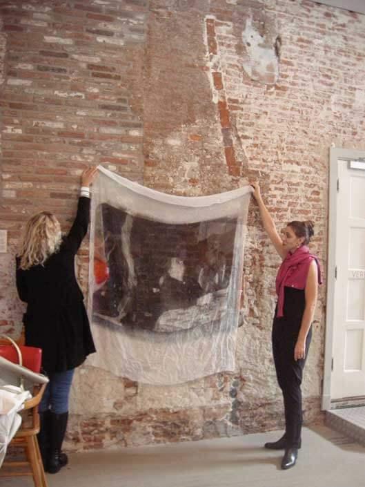 Twee vrouwen houden een dun doek op tegen een ongepleisterde muur. Op het doek staat een vrouw afgebeeld die in trance is.