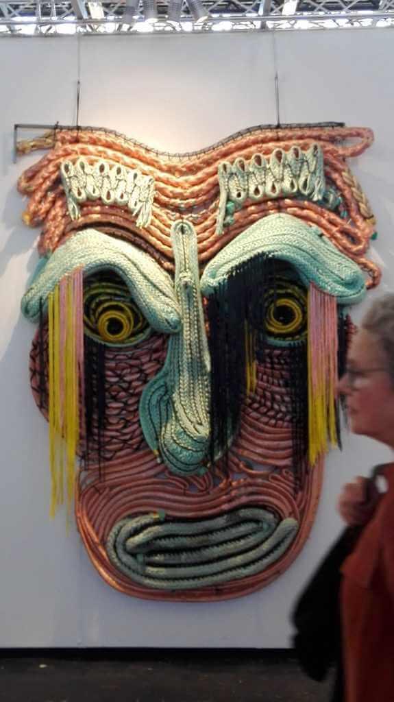 Vrouw loopt langs een groot masker van kunstenaar Joana Schneider dat aan een wand hangt.