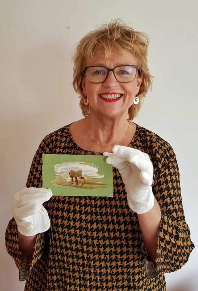 Lachende Mirjam Hijstek houdt met witte handschoenen een kleine tekening van Beth Namenwirth op.