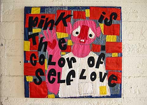 """""""Pink is the color of self love"""" staat op een klein wandkleed in vrolijke kleuren gemaakt door Bas Kosters."""