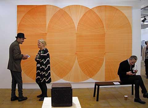 Drie mensen voor een wandvullend abstract oranje schilderij van Thomas Trum op de kunstbeurs Art Rotterdam, februari 2020.