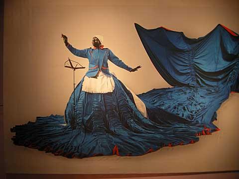 Zwarte vrouw in blauw theatraal huishoudsteruniform met hoepelrok en grote vissenstaart houdt een dirigeerstokje omhoog voor een lege muziekstandaard.