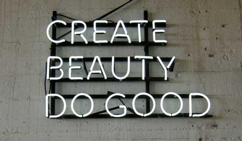 """""""Create Beauty - Do Good"""" is de tekst die staat geschreven in witte neonletters tegen een betonnen muur."""