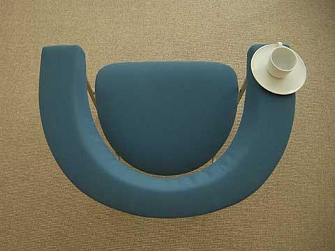 Blauwe stoel van Rudolf Wolf van bovenaan gezien met rechts een witte kop en schotel op de brede leuning.