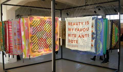 Display met kleurige zijden shawls, bedrukt met tekst of abstracte motieven.