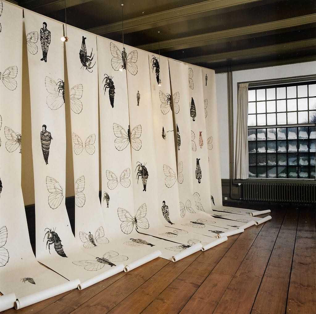 Losse rollen papier van plafond tot vloer met daarop o.a. vlindersoldaten