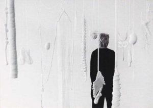 Vrouw staat in ruimte met witte voorwerpen die in de lucht hangen